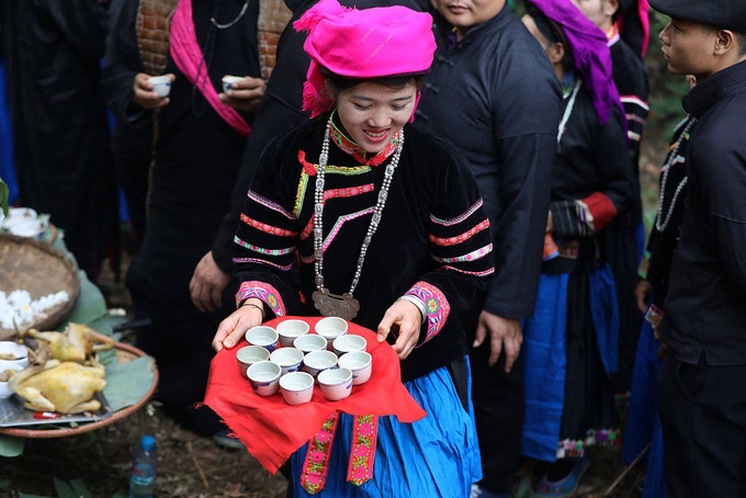 Pu Peo women hand cups of wine to the attendees to mark the end of the ceremony.